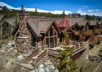 Large chalet-style home with several stone patios and wooden decks and snow-covered mountains in background