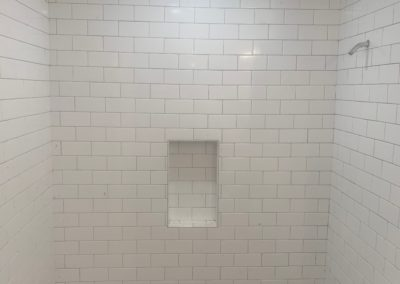 Shower walls stripped to studs and insulation above bathtub with scars from glass door tracks