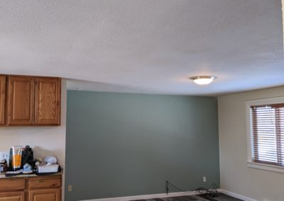 Looking into open kitchen and living room with patched ceiling drywall where wall was