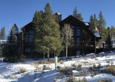 Pine tree on snowy hill in front of classic log-style home with large deck and large windows