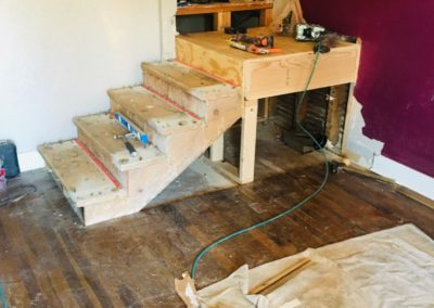 Open framing of staircase with 4 stairs and landing with tools on top