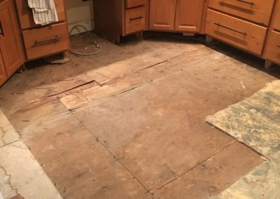 Kitchen floor in front of cabinets removed to reveal water damaged subfloor boards