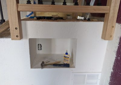 Hammer and glue outlet in drywall cubby below wooden handrail posts and above heat vent grate cover