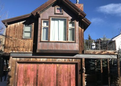 House sided with used snow fence and contrasting materials on garage doors deck handrail and chimney