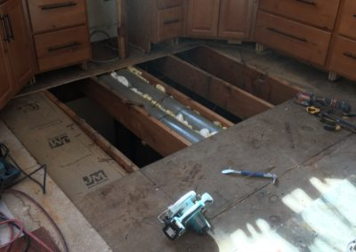 Subfloor in front of kitchen cabinets with tools and 4 foot by 8 foot hole cut to floor joists