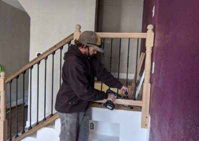 Builder uses power drill to secure metal baluster to wooden handrail