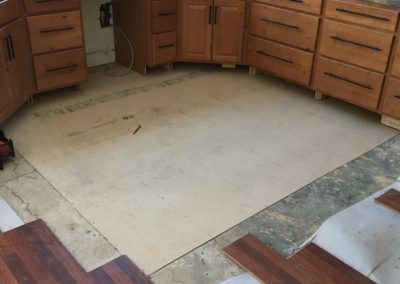 New plywood subfloor in front of kitchen cabinets