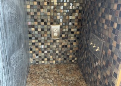 Tile and switch covers on back and right wall of open kitchen cabinet