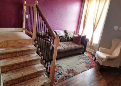 Couch and arm chair on top of rug to the right of staircase in room with dark hardwood floors