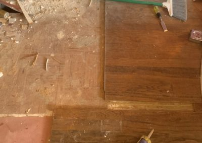 Tools on hardwood floor with uneven edge and a missing floor board