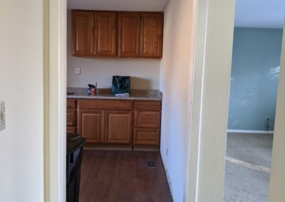 Kitchen cabinets and vinyl floor on left and living room with stained carpet on right with wall and doorway between them