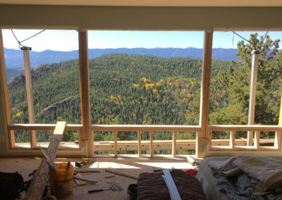 Forested mountains and scaffolding out exterior wall with doors and windows removed