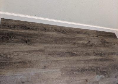 Wood-grained vinyl floor with baseboard trim