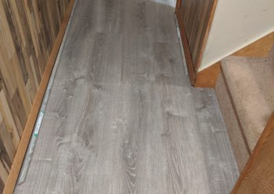New vinyl floor in hallway and bathroom with transition piece at different laundry room floor