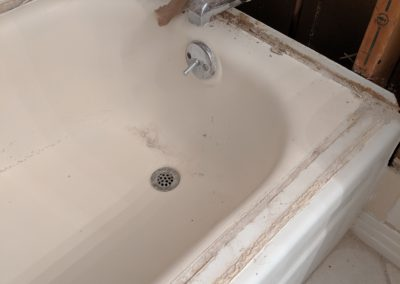 Damaged bathtub with walls above it stripped to the studs and insulation and plumbing exposed