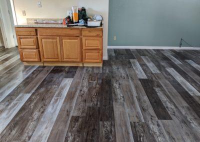 Wide-plank vinyl flooring covers open kitchen and living room floors