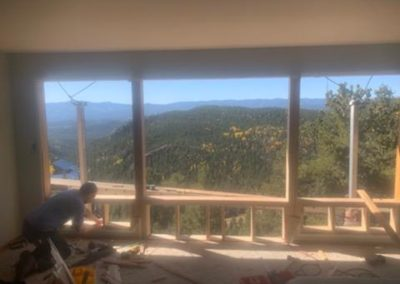 Framing open exterior wall with scaffolding and forested mountains outside