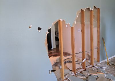 3. Exposed studs and electrical outlets in partially-demolished wall with drywall debris on floor on both sides