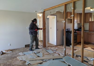 Man uses crowbar to remove framing in corner of demolished wall with some studs removed and drywall debris on subfloor