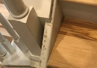 Trim on stair landing has chipped paint and holes
