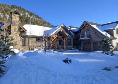Snow on ground and roof of log-sided home with timber and stone details