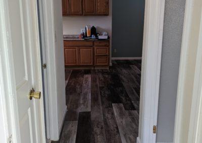 Wide-plank vinyl flooring runs up hallway into open kitchen and living room