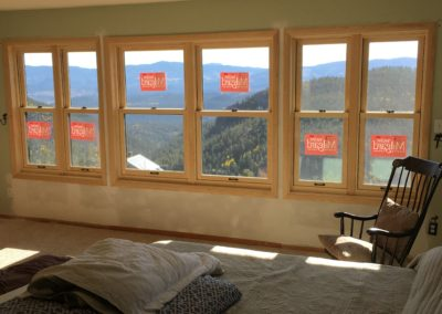 6 new windows and drywall with forested mountains outside