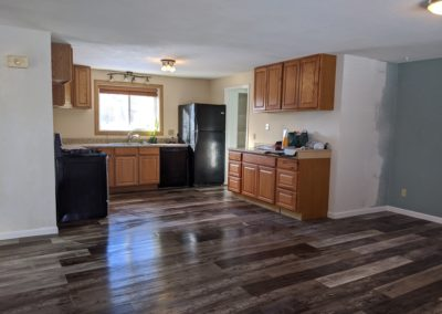 5. Open living room into kitchen and hallway with new floor and patched ceiling drywall