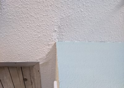 Uneven ceiling drywall with fan vent and patched crack