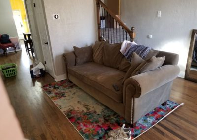 Couch and rug in front of stairs in living room with hardwood floors