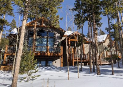 House with log details on handrails and posts for 5 decks and 2 roof peaks on snowy hill with trees