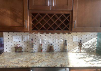 Kitchen backsplash with shiny gold square tiles in between diamond-shaped tiles below diamond-shaped wine rack