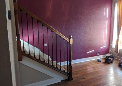 Carpeted staircase with handrail lands in room with hardwood floors