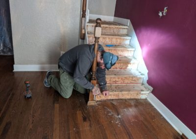 Builder unscrews handrail post from floor at bottom of staircase