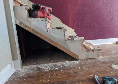 Toolbag and tools on top of raw wooden stairs with open triangle gap under steps