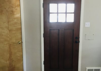 New, dark wood 2-panel Shaker front door with 6-pane glass window inside house