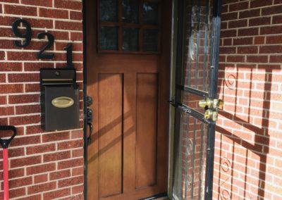Open security door and new, dark wood 2-panel Shaker front door with 6-pane glass window at brick house