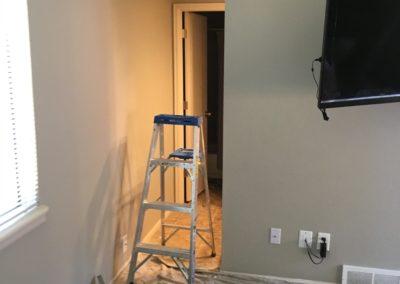 Ladder in gap between 2 walls tools on top of drop cloth