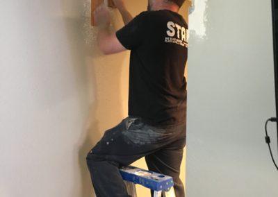 Man on ladder sanding wall