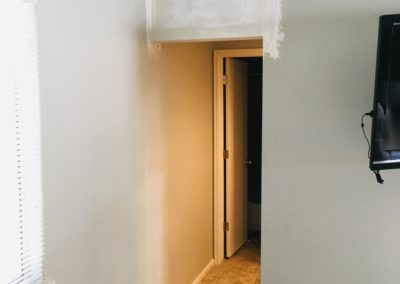 Drywall patch at top of gap between walls to make new doorway