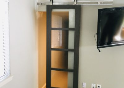 Partially-opened barn door with 4 glass panels on overhead track in new drywall