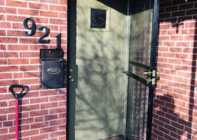 Open security door and front door with 6-inch square window at brick house