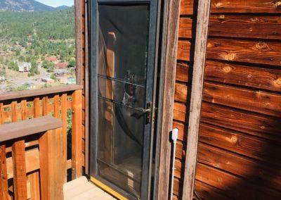 Broken screen in opened door on deck of home with wood siding
