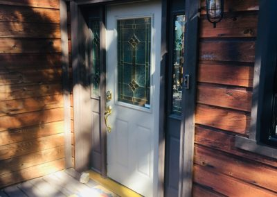 Front door with stained glass window and 2 stained glass sidelight windows at home with wood siding