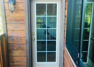 Door with 10-paned glass window on deck of home with wood siding