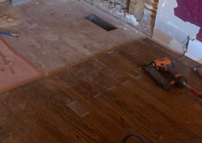 Nailgun on patched hardwood floor with even edge and perfectly matched boards