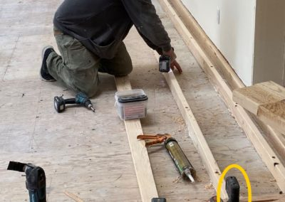 Builder attaches board to subfloor with laser on top of board