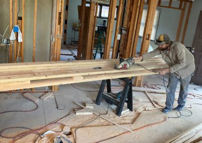 Builder uses electric handsaw to cut long boards on top of work horses in room with exposed beams, floors, and insulation