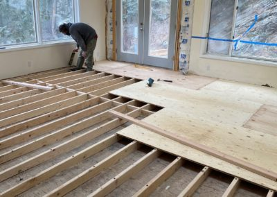 New plywood covers grid of framing boards in room with exposed insulation around French doors