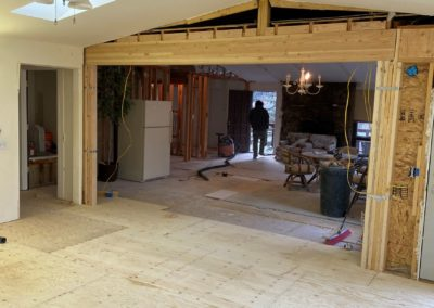 View across room of new plywood beneath new laminate beams